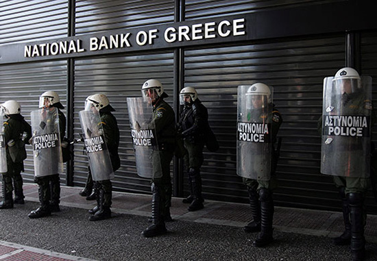Police guard a Greek bank earlier this year during protests by striking Greek workers against continued government austerity.