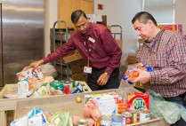 Latchman Hiralall, manager of Boston Medical Center's Preventive Food Pantry (left), and food pantry assistant Juan Carlos Turcios prepare a cart of food for a patient. Photos by Dana J. Quigley