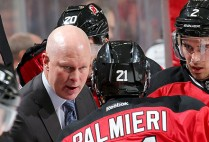 Head Coach of the New Jersey Devils John Hynes talks to his players on the bench during a timeout