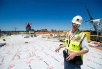 Al Hartshorn, Shawmut Design and Construction senior project superintendent, stands on Myles Standish Hall's new roof
