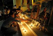 Cubans mourning light up candles in front of photos of Castro