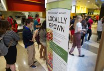 "Boston University students file past a ""Locally Grown"" sign in a BU dining hall. BU Dining Services hit its goal of providing 20% sustainable food three years early."