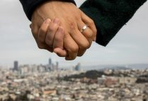 a married couple in san francisco california hold hands with the city in the background