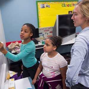 Aurora Kesseli with third-graders Amaria Smith (left) and Cassandra Riley as they work on an experiment at the Girls Science Club.