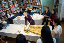 Lauren Whitley, senior curator of textile and fashion arts for the MFA, shows students a mid-18th-century English brocaded silk dress, once worn by Lydia Catherine, Duchess of Chandos.