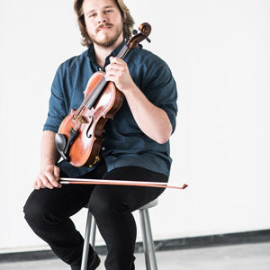 Contemporary music composer Nicholas Quigley poses with violin