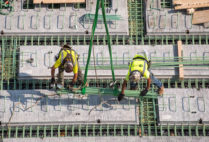 two construction workers balance on a sea of green pegs