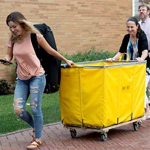 Student pushing move-in cart with her parents