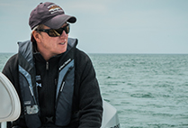Greg Skomal, Atlantic White Shark Conservancy shark researcher sitting on a boat during an expedition to track Cape Cod sharks