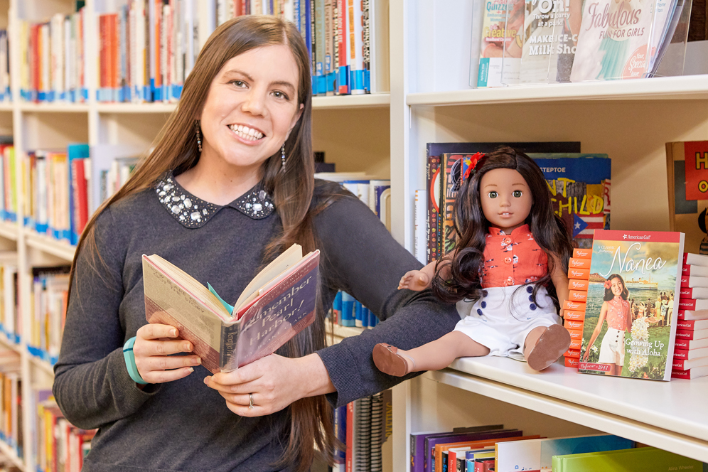 Tessa Croker, a PhD student in BU's American and New England Studies Program, poses alongside shelves of books and an American Girl Doll. She recently joined the iconic doll company American Girl, where she ensures the historical accuracy of its products.