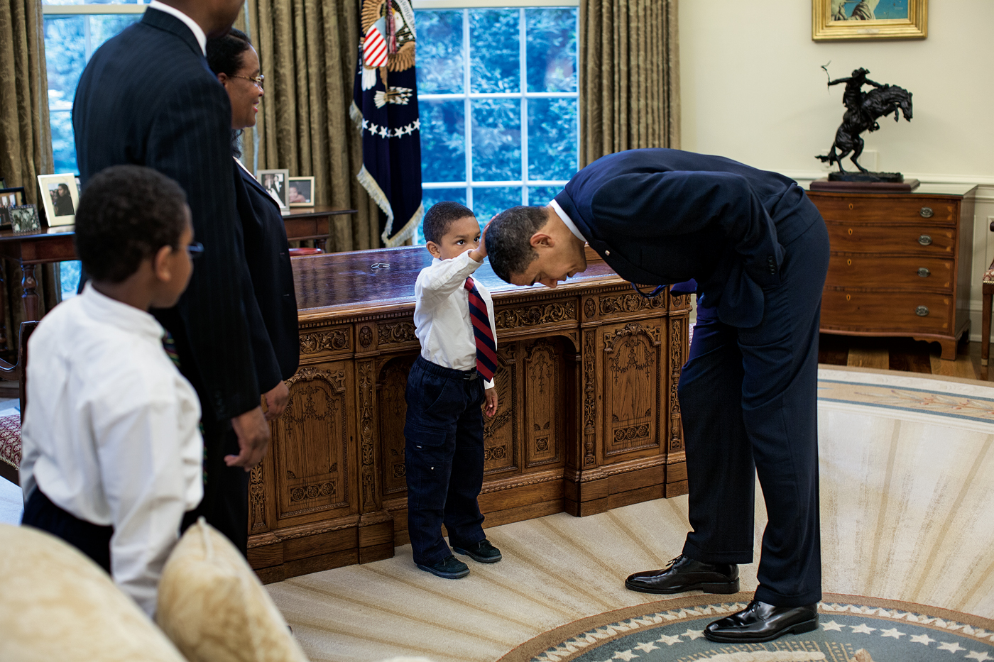 Photograph entitled Hair Like Mine taken by official White House photographer Pete Souza of President Barack Obama bending down so a young African American boy can touch his head.