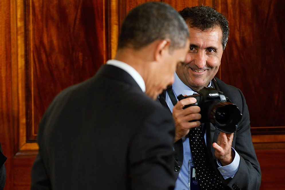 White House photographer Pete Souza, camera ready, with President Obama during an event celebrating the Affordable Care Act in 2010