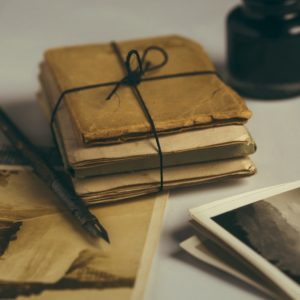 inkwell, pen, parchment and postcards