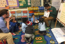 BUILD tutors and students gather on the carpet to listen to a book read aloud.