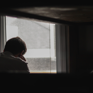 image of a man staring out of a window sitting in a dark room.