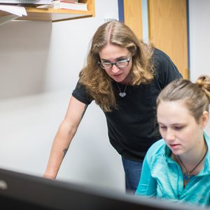 Emily Ryan and a graduate students look intently at a computer screen
