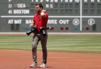 Billie Weiss, the Red Sox manager of photography, on the field wearing multiple cameras