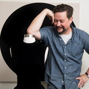 Jason Chase, painter and artist-in-residence at NanoLabs, poses with a black dress painted with Singularity Black paint that will be on display at the Boston Museum of Fine Arts