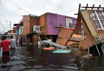 People walk in a flooded street next to damaged houses in Juana Matos, Catano, Puerto Rico, on September 21, 2017, after Hurricane Maria