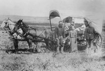A family during the Great Western Migration, 1866, stands alongside their covered wagon.