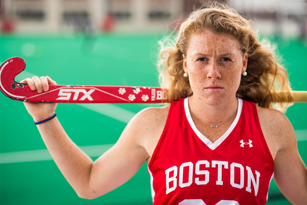 Portrait of Ally Hammel, Boston University Terriers field hockey NFHCA All-American, wearing her BU jersey and holding her stick on her shoulders.