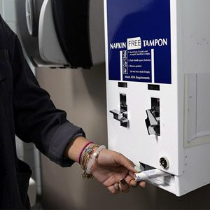 A young woman removes a tampon from a blue and white free tampons dispenser in a restroom.