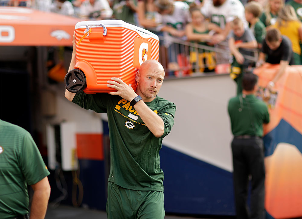 Sports dietitian Adam Korzun carries an orange cooler while walking the sidelines during a Green Bay Packers game.