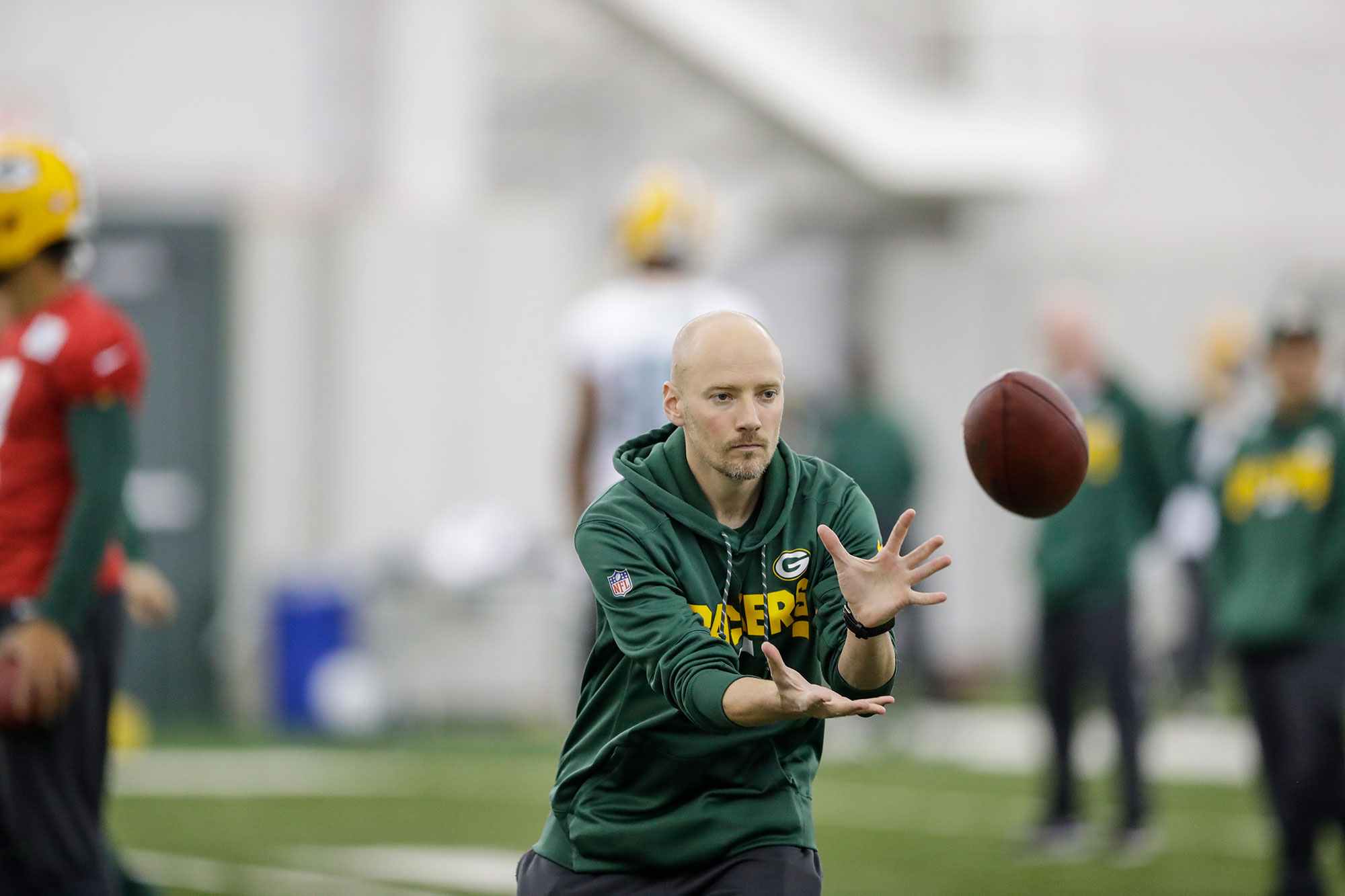 Adam Korzun, director of performance nutrition for the Green Bay Packers, catches a football during a Packers practice.