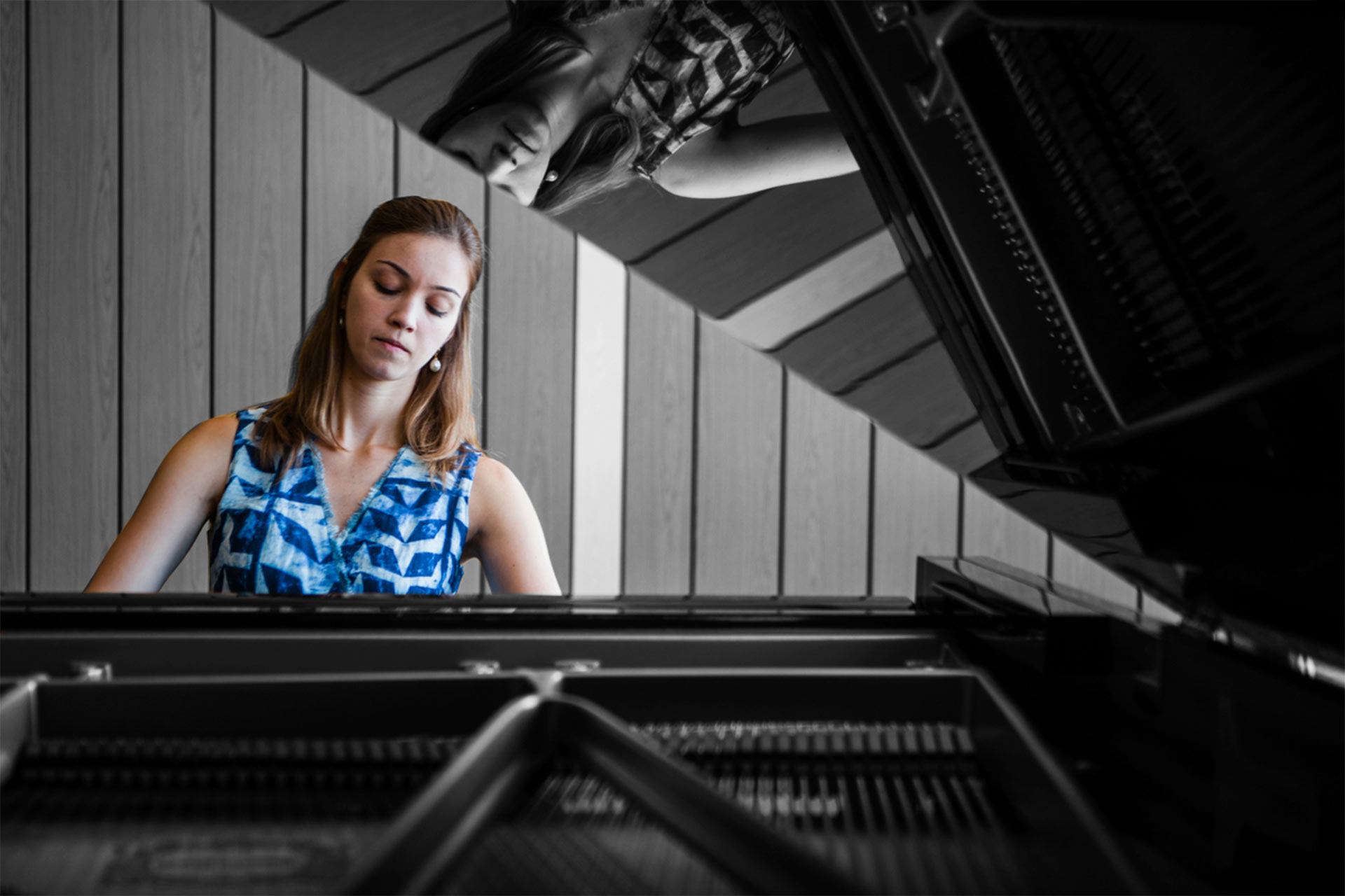 Bendada Music Festival founder Inês Andrade performs on a black grand piano.Photo taken from behind the piano looking at the performer.