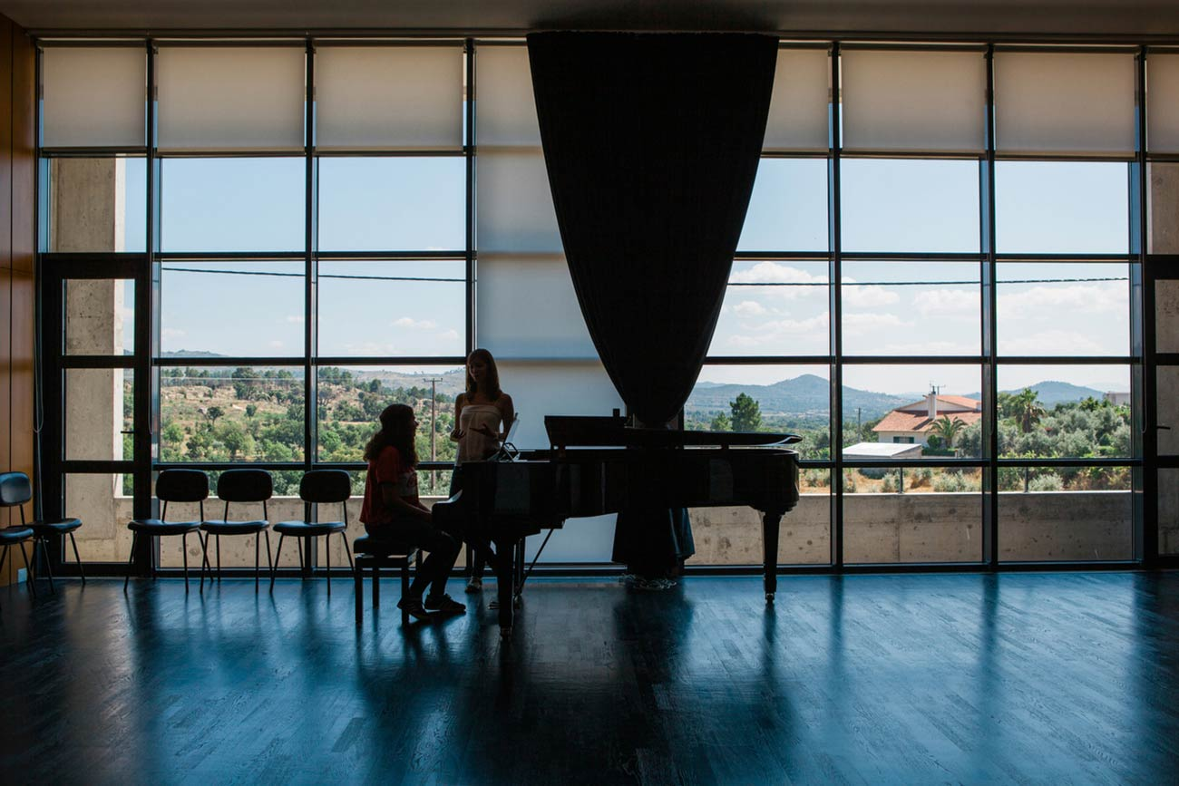 Full color slideshow photo of Bendada Music Festival founder Ines Andrade leading a piano lesson with a student in the Casa Da Musica Da Bendada concert hall. The student, sitting at a baby grand piano, and teacher are silhouetted against floor to ceiling windows with a vista view of Bendada and the distant Portugal mountains.