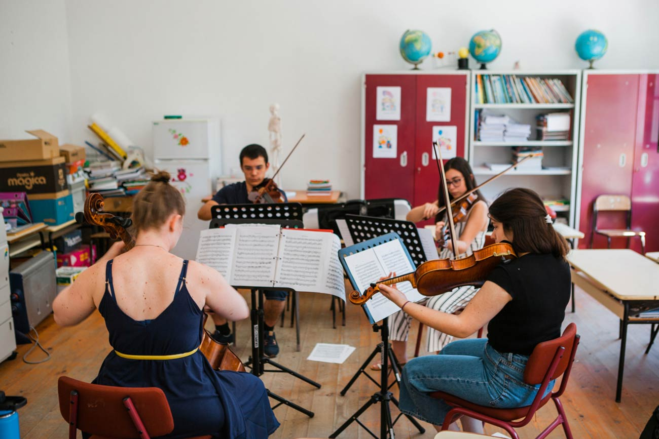 Full color slideshow photo of Cello instructor Gracie Keith leads a chamber music quartet, with students playing two violins and a viola, in playing Beethoven's String Quartet No. 2 in G major.