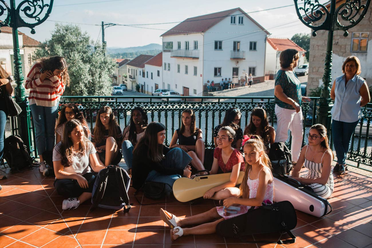 Full color slideshow photo of Bendada Music Festival students and Bendada villagers gathered sitting and standing in the shade of the coreto bandstand watching a festival performance.