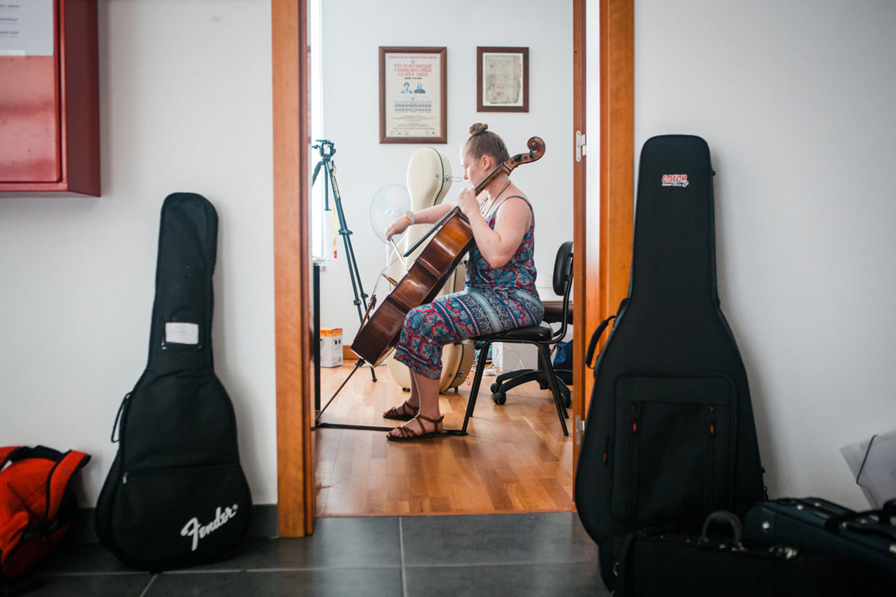 Full color slideshow photo of Cello instructor and Boston University student Gracie Keith practicing in the office of the Casa Da Musica Da Bendada.