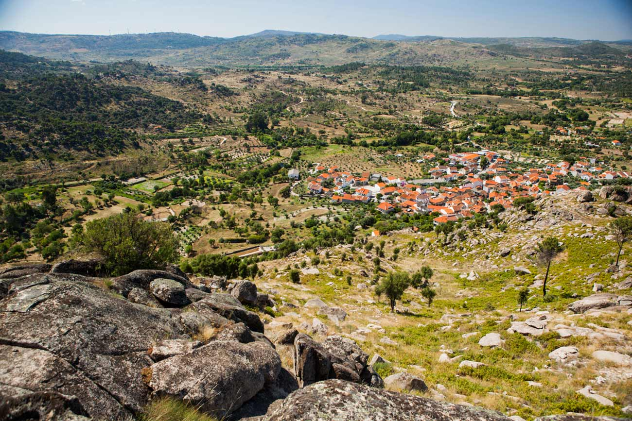 Full color slideshow photo showing a stunning view looking down on the village of Bendada, Portugal from a mountain side vista. Blue skies, green trees, pastures and mountain sides, and the terra-cotta roofs and white buildings of Bendada can be seen.