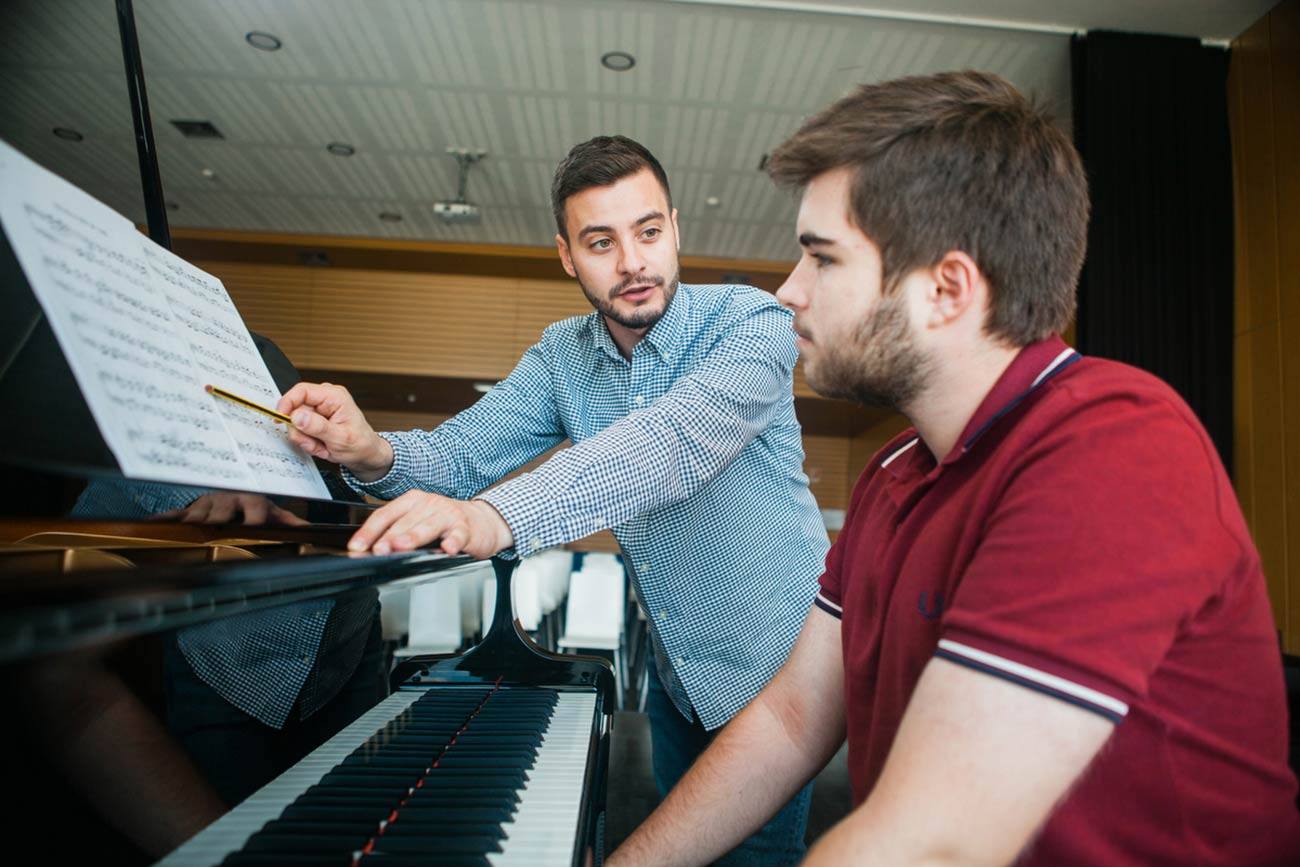 Black and white slideshow navigation image of Boston University student Edoardo Carpenedo, a Bendada Music Festival co-founder and instructor, leading a piano lesson with a student from Fundão, Portugal.