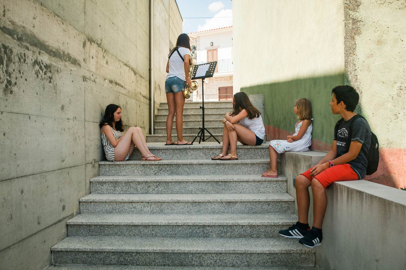 Full color slideshow photo of a female Bendada Music Festival student practicing her saxophone on a stairwell in between two buildings while four of her friends listen and watch.