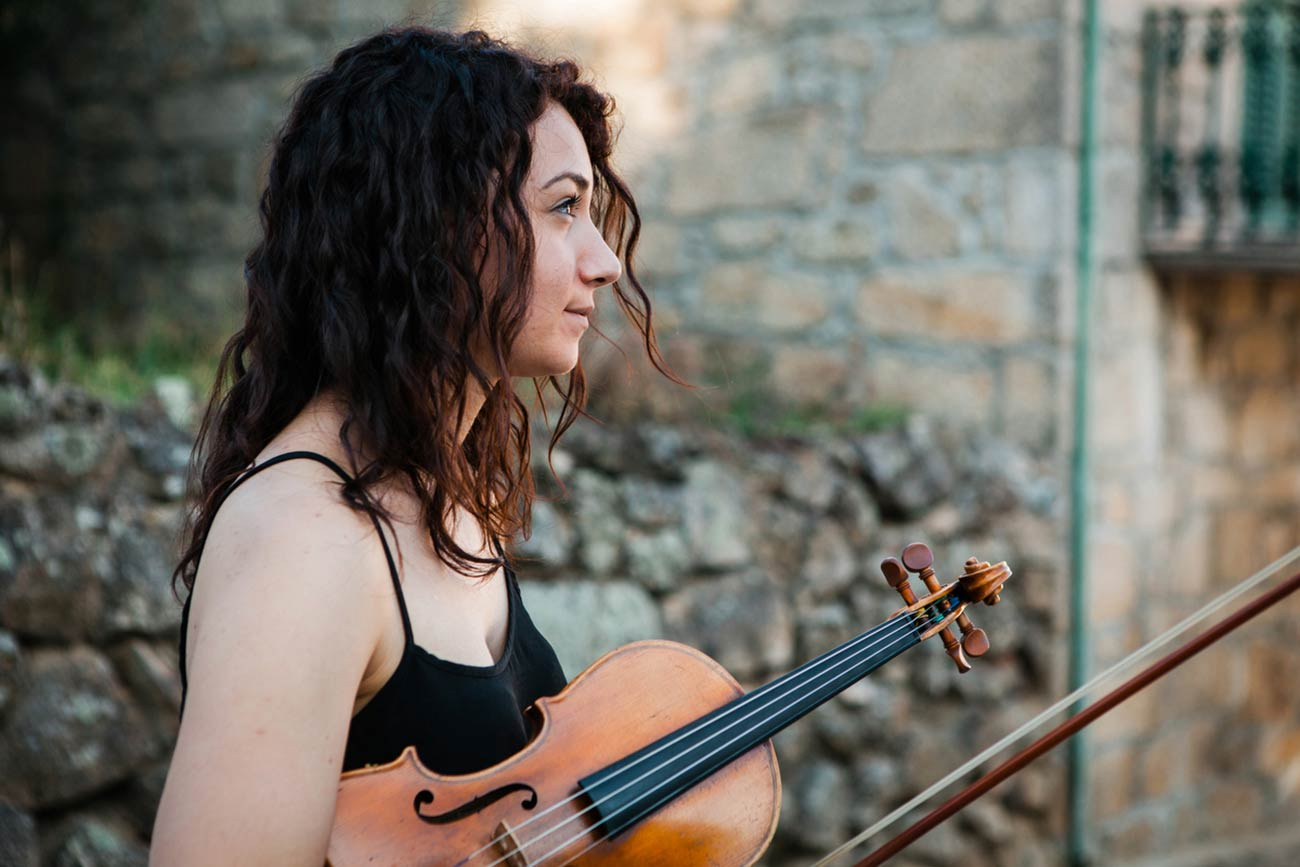 Full color slideshow profile portrait of Francesca Baldo, a violin student from Padua, Italy, holding her violin and bow as she watches her fellow music students perform in Bendada's village square.