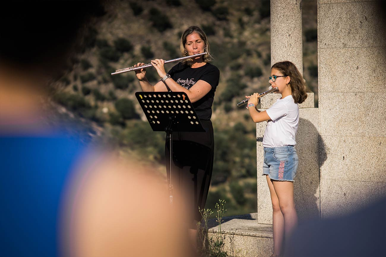 Full color slideshow photo of Bendada Music Festival Flute instructor Margarida Quitalo her student Beatriz Leal standing side by side in front of granite columns performing on a hilltop overlooking the village of Bendada.