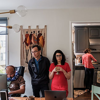 Craig Cloutier, Rahul Desikan, Iris Broce, and Chin Hong Tan work in Desikan's office while Desikan's wife Maya makes a meal in the kitchen.