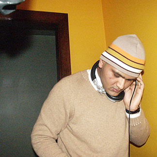 Rahul Desikan holds headphones to his ear while deejaying.