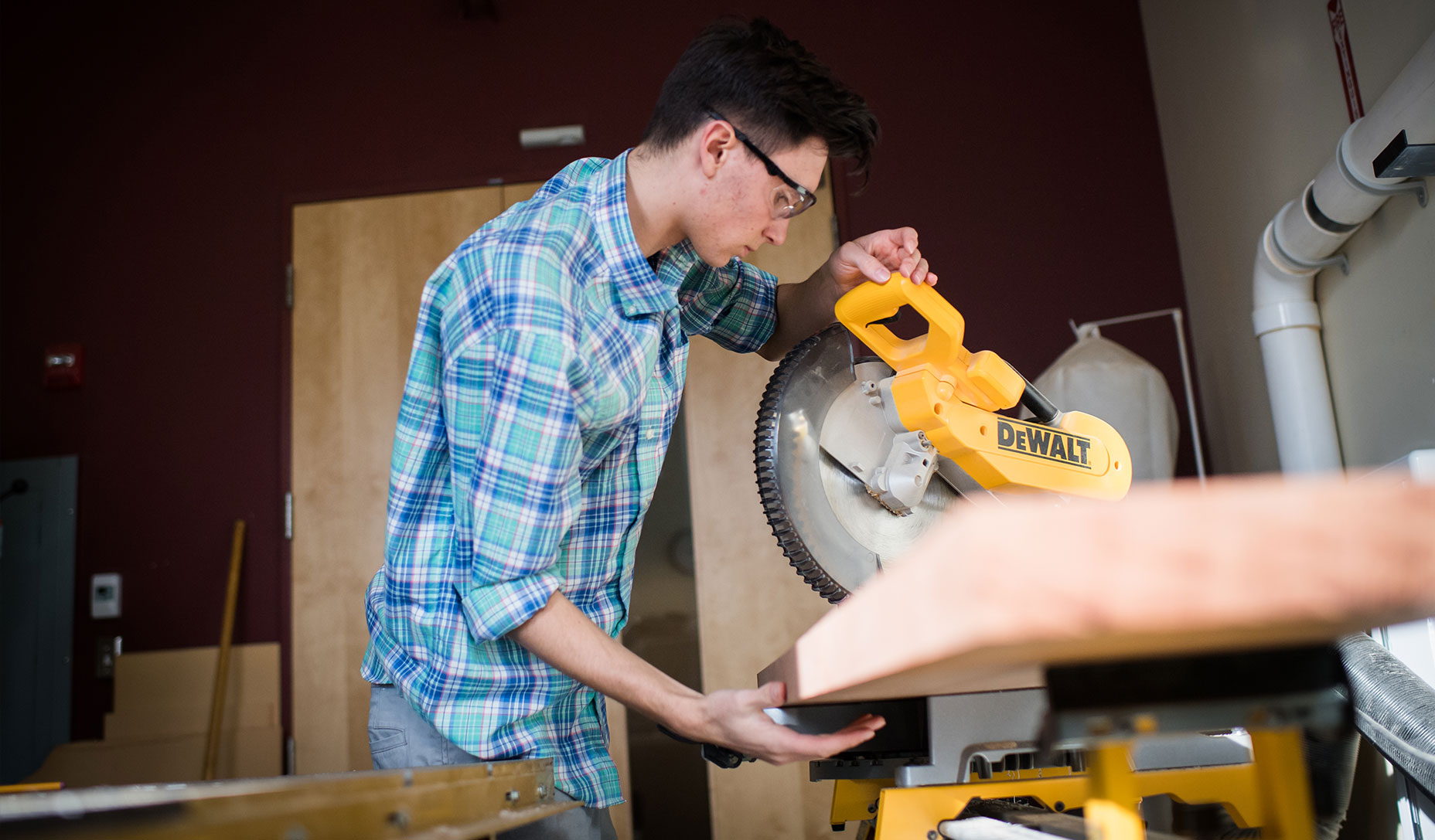 Woodworker Justin Fiaschetti uses a saw in the Fiaschetti Woodworking workshop.