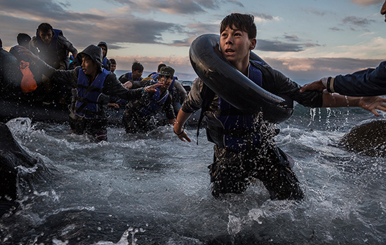 Tyler Hicks ('92) captured desperate migrants wading ashore in Lesbos, Greece, as part of a New York Times Pulitzer-winning package. Photo by Tyler Hicks, New York Times
