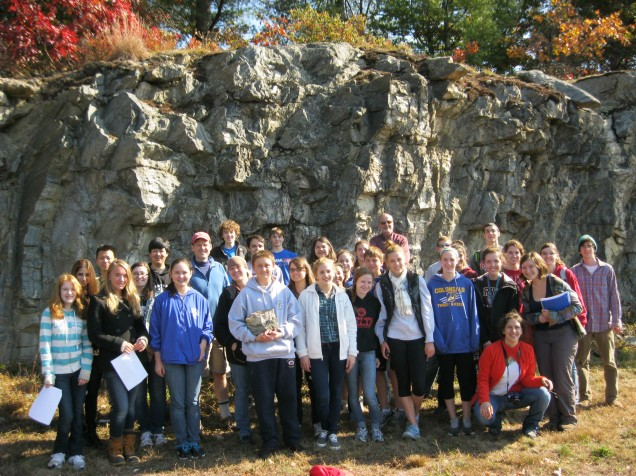Students and Faculty gather for a group shot in front of a rock formation.