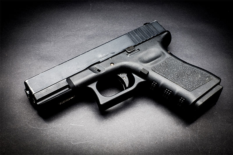 Black handgun lying on a black background