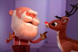Video still from the 1964 Rudolph the Red-Nosed Reindeer tv special showing Santa Claus talking to Rudolph with his blinking red nose.