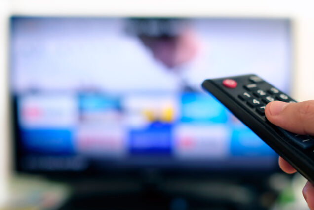 A photo of someone pointing a remote at a television screen