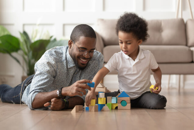 A photo of a father and son playing with wooden blocks together
