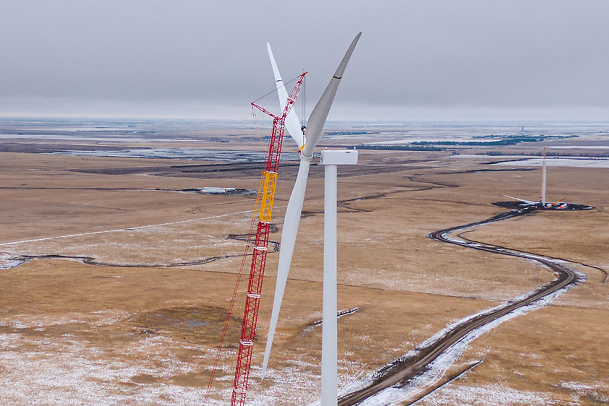 A photo of a wind turbine with a crane working on it