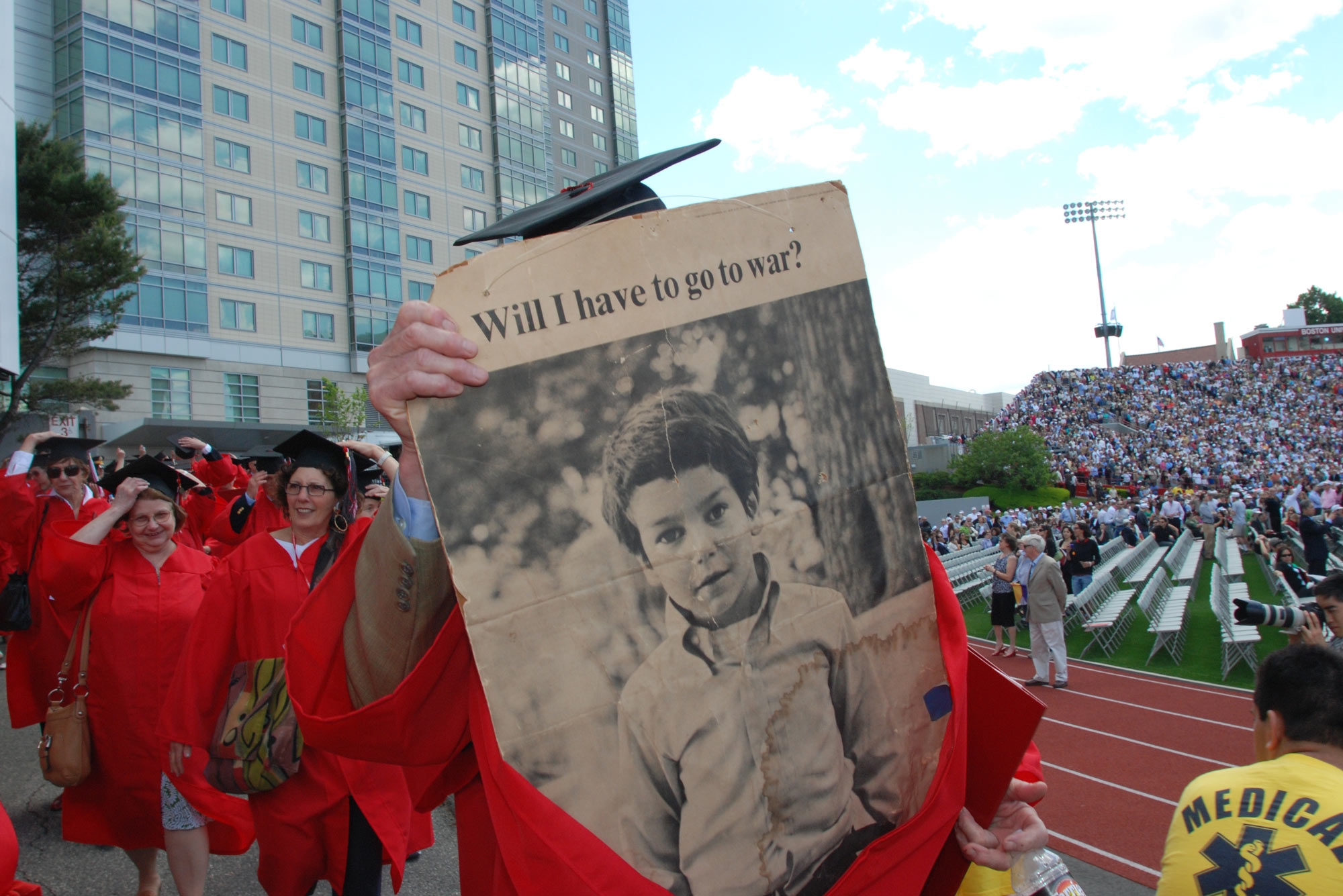 "A photo of the Class of 1970 Convocation in 2010. A graduate holds up a newspaper that reads ""Will I have to go to war?"""
