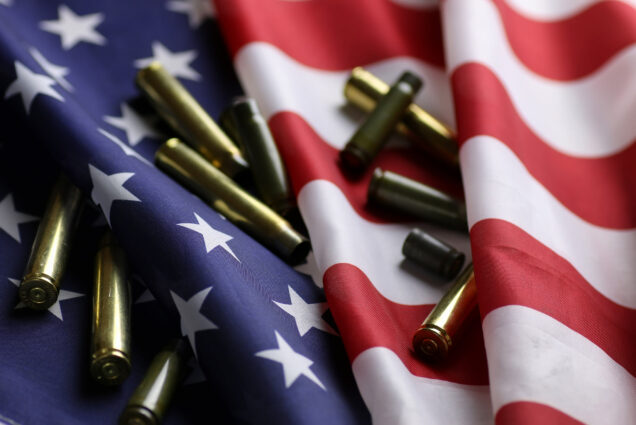 A photo of an American flag with bullet shell casings scattered on top of it
